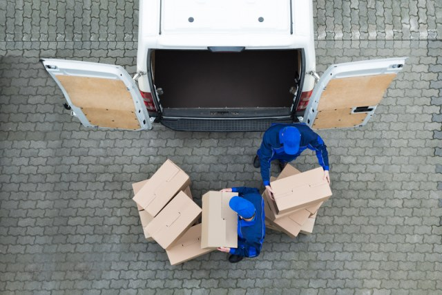 Delivery people wearing blue stacking cardboard boxes
